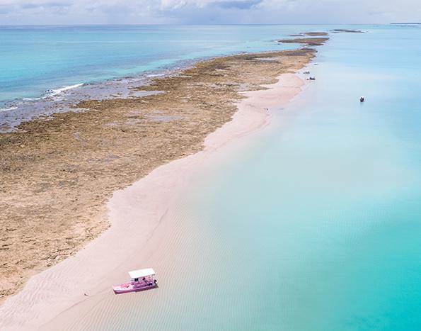 foto aérea de um banco de areias e barreira de corais em meio ao mar