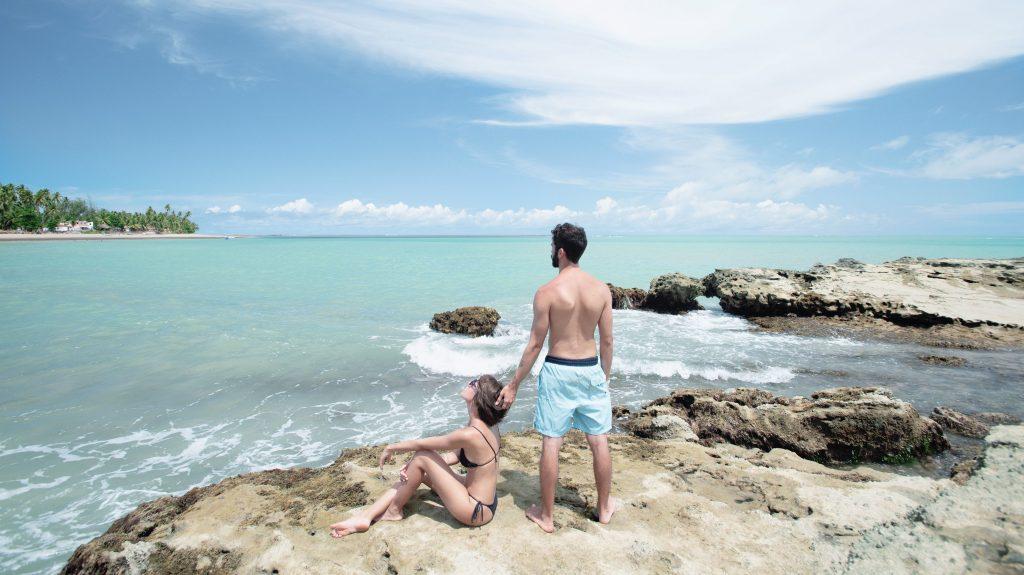 casal em cima das formações rochosas que compõem a praia de barreiras do boqueirão