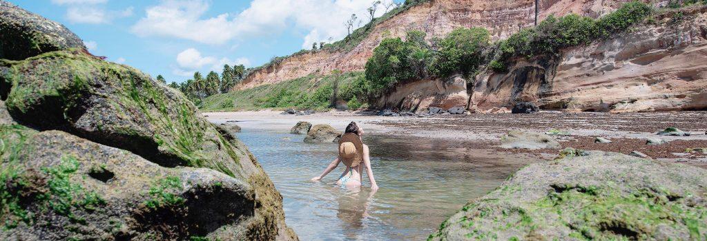 mulher tomando banho nas águas da praia de barreiras do boqueirão