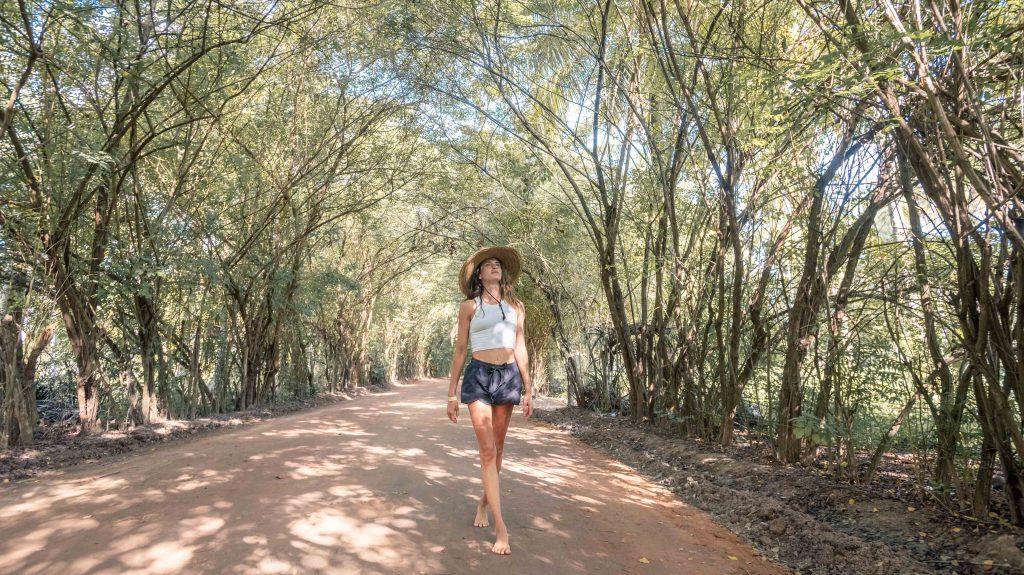 mulher no meio da estrada onde a copa de árvores se encontram formando um túnel verde