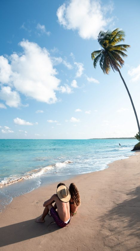 casal sentado na beira da praia do patacho
