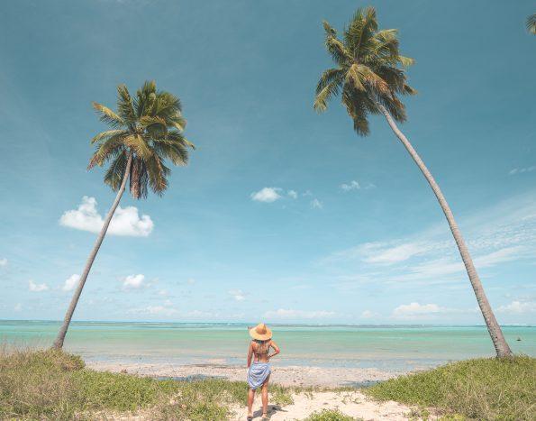 mulher em meio a dois coqueiros olhando para o mar da praia do patacho