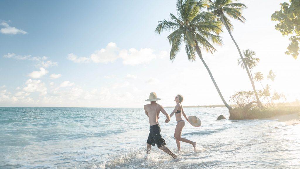 casal correndo feliz para dentro do mar no pôr do sol da praia do patacho
