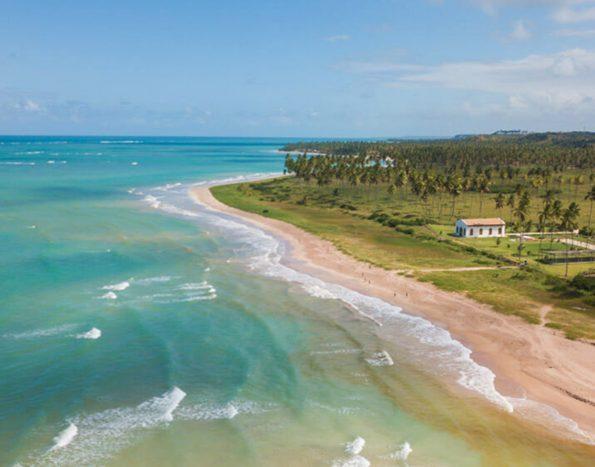 foto aérea da praia de são miguel dos milagres com o mar turquesa e a igreja de longe