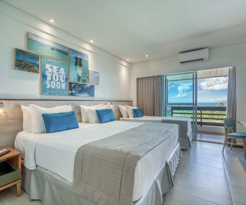 Apartamento Standard, com uma cama de casal e uma de solteiro, mesa para apoio, mesa de cabeceira, varanda com vista mar e piscina e decoração em tons de azul.
