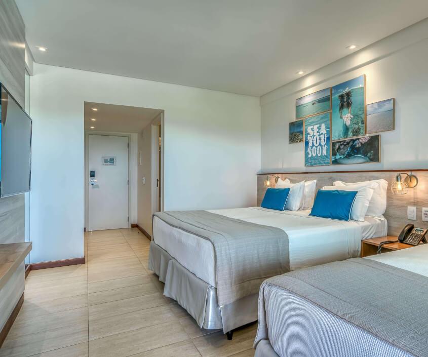 Apartamento Standard, com uma cama de casal e uma de solteiro, TV Smart, vista para entrada do quarto e decoração em tons de azul.