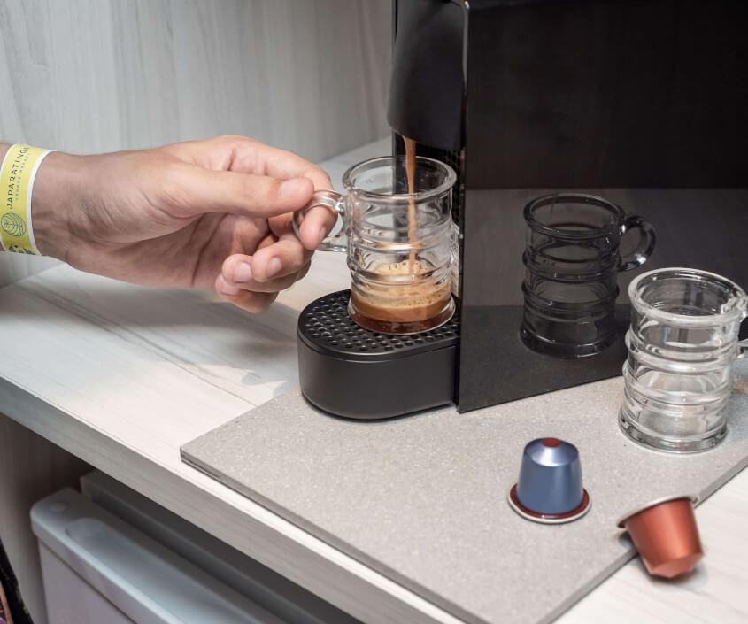 Cafeteira Nespresso servindo café e mão segurando a xícara. Cápsulas e outra xícara ao lado.