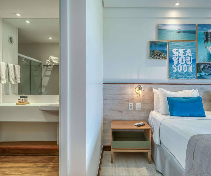 Entrada do banheiro com amenities Natura Ekos, mesa de cabeceira com luminária e controles, e cama com quadros decorativos acima de temática mar.