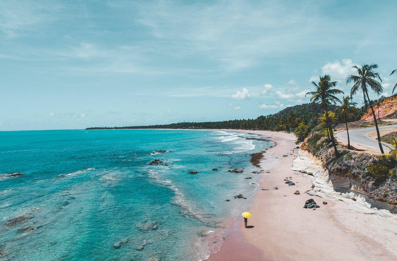 Praia com pessoa caminhando com guarda-sol