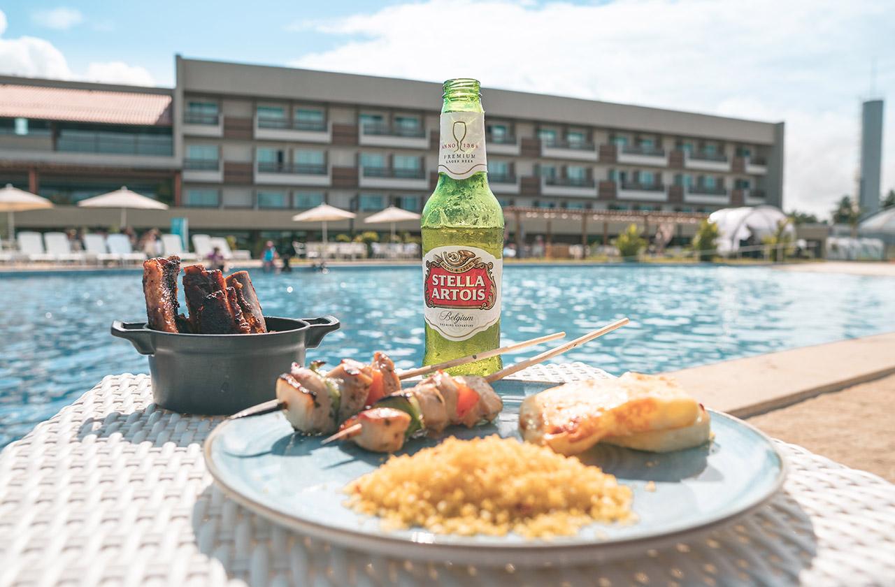 Stella Artois, espetinho e costela assada à beira da piscina no Japaratinga Lounge Resort