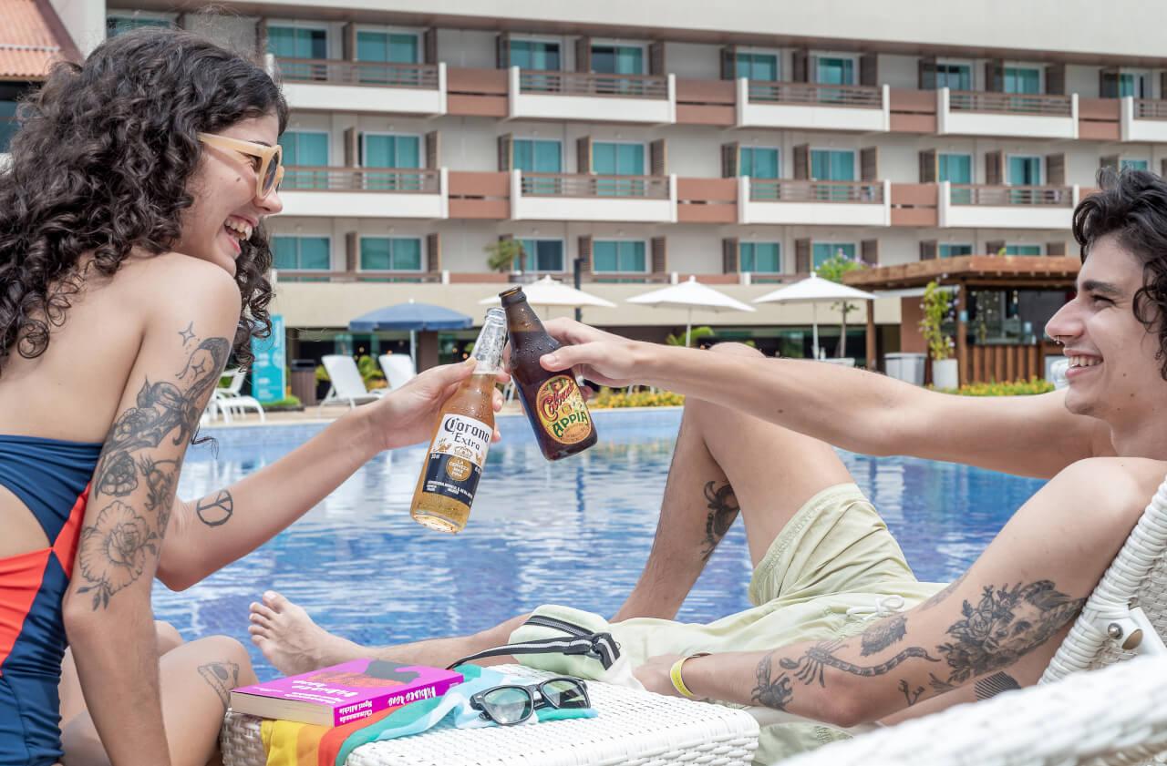 Cervejas Bohemia, Skol Beats, Colorado Appia, Becks, Colorado Ribeirão, Budweiser, Corona, Stella Artois, e Original, com piscina ao fundo.
