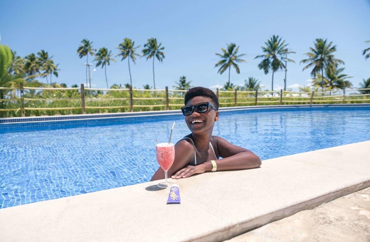 Mulher tomando drink na borda da piscina