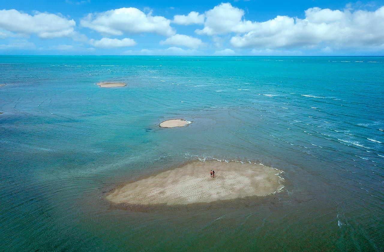 Bancos de areia cercados por mar azul
