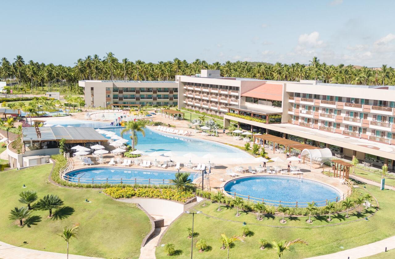 Imagem aérea das piscinas e blocos de apartamento do Japaratinga Lounge Resort