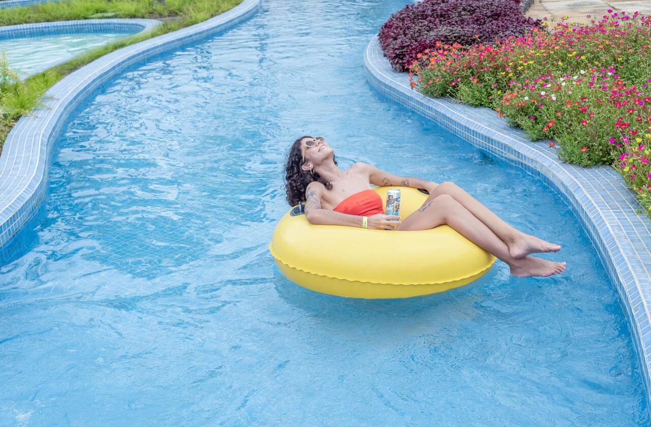 Mulher deitada na boia na piscina de Rio Lento com uma cerveja Colorado lata na mão