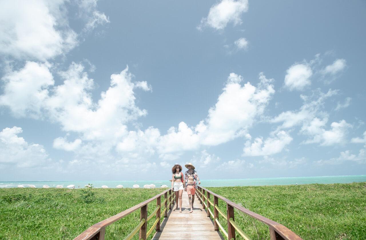 Casal caminhando pela passarela da Vila da Praia no Japaratinga Lounge Resort